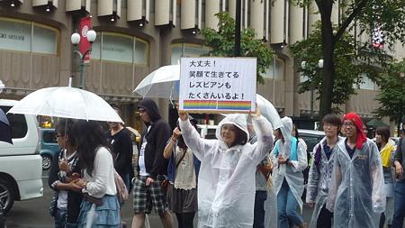 プラカード「大丈夫!笑顔で生きてるレズビアンもたくさんいるよ!」を掲げる人。
